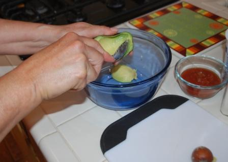 Scooping flesh out of avocado